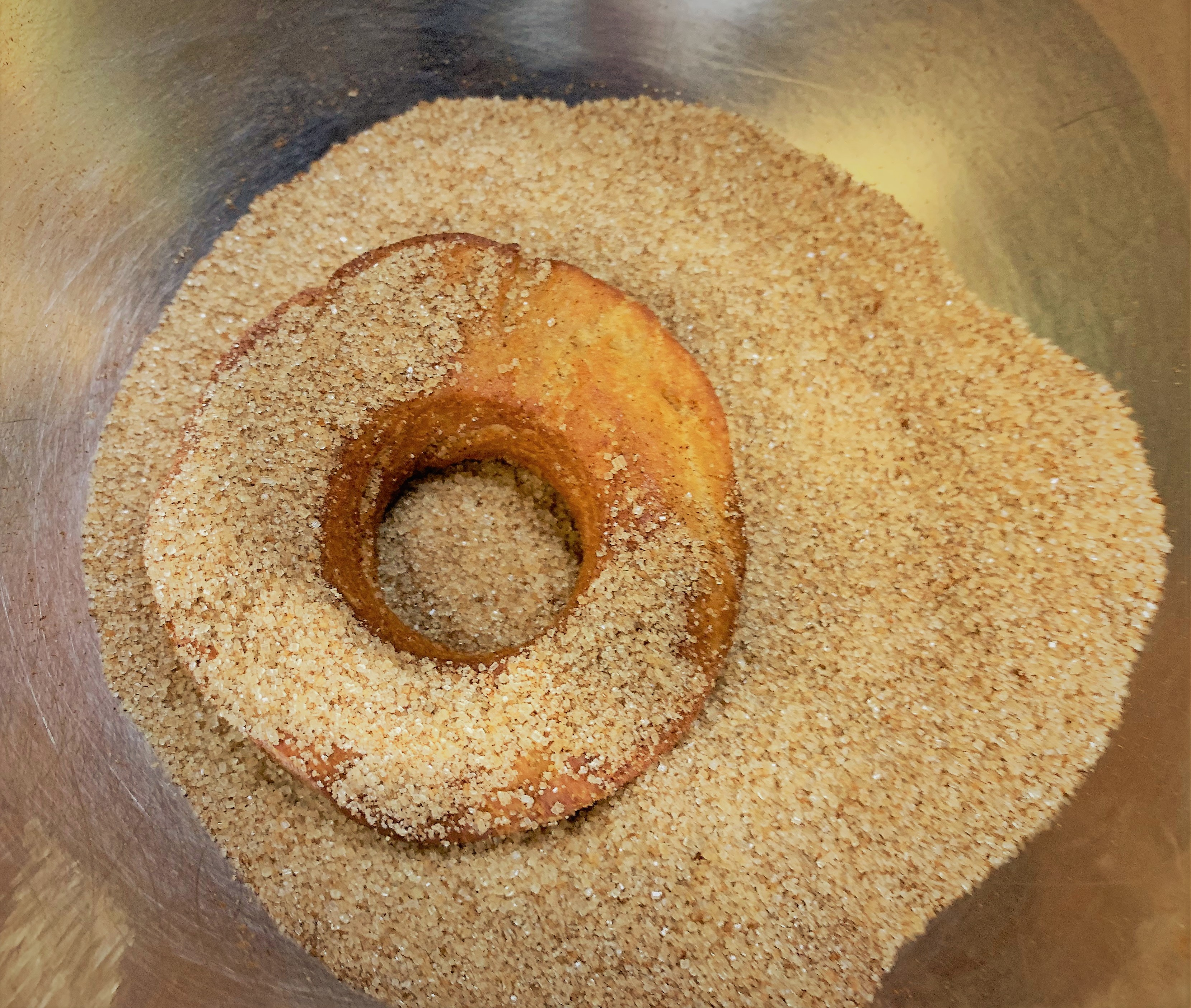 Tossing the doughnuts in cinnamon sugar